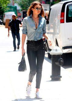 Street style look camisa jeans, calça resinada preta, tênis branco e óculos espelhado.