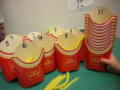 """Teaching one-to-one correspondence.  I got the fry holders for free at McD's.  The """"french fries"""" are just made out of cut up yellow foam.  The kids love this."""