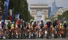The peloton pass along the Champs-Élysées with the Arc de Triomphe in the background.