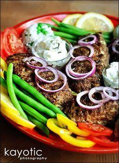 Bifteki  2 slices of white bread  1 pound ground beef  1 small onion  1/2 tsp thyme  1 tsp oregano  1 tsp parsley  1 tsp mint  1 tsp salt  1 egg  pepper  Feta cheese  Optional: 1 tbsp tzaziki  Optional: garlic
