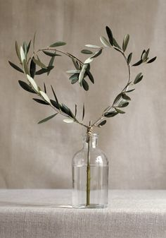 The guest book table will have a clear wine bottle with olive branches shaped into a heart.