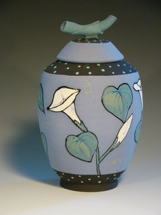 """Lidded jar.  Morning Glory pattern. Wheel thrown clay with layered matte glazes.  Approximate size is 10"""" h X 6"""" dia. Not food safe.  $135."""