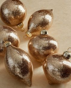 A dimensional coating of hand-applied glitter brings sparkling depth to any tree-trimming collection. With simple ball, onion and teardrop shapes, this collection of mouth-blown glass ornaments complements both traditional and modern styles.