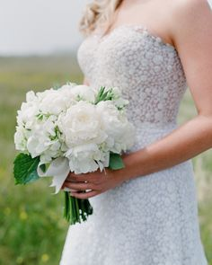 """The bride carried a bouquet of white peonies and sweet peas by Mindy Rice. Of her Mira Zwillinger dress, the bride said, """"I am definitely not a blingy person, but the shine of this dress felt sophisticated, and classic in its own right. Peony Bouquet Wedding, White Wedding Bouquets, Wedding Flower Arrangements, Wedding Flowers, Wedding Dresses, Bridal Bouquets, Sweet Pea Bouquet, Wedding Flower Inspiration, Wedding Ideas"""