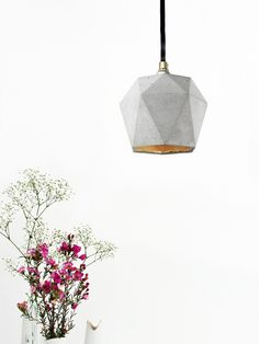 [T2]  The triangualte pendant lamp [T2] is cast from a light grey concrete. It combines noble gold with rough concrete into a timeless and elegant designer lamp. The high quality gilding of the...