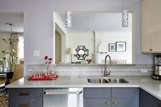 Unable to completely remove a load bearing wall to create an open floor plan, Sarah Richardson widened a doorway and cut a large serving window out of the wall between this kitchen and living room to create a semi-transitional space. She updated the kitchen with a gray subway tile backsplash, new countertops and stainless steel appliances for a chic, contemporary look. As seen on season 1 of Sarah Sees Potential.