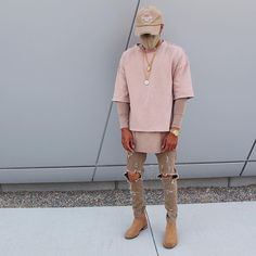 Neutral all nude colors and outfits are very popular for the the fall season for young men. Paired with ripped skinny khakis and tan Chelsea boots. Lastly the layered look with a short sleeve crew neck and long sleeve with a dad hat and chains pull the whole look together. Markus Stoll