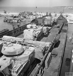 Grant tanks, including flail variants, embarking onto a landing craft at Tripoli, 3 July 1943.