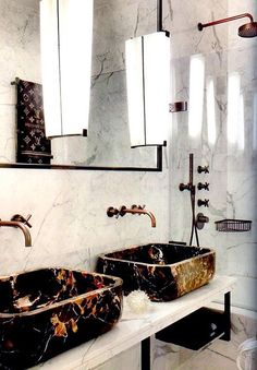 A perfect mix of marbles, with sinks designed by Colin Cuarto, and sconces reclaimed from an italian hotel...