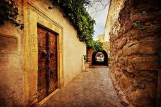 Narrow street in the souk of Hammamet, Tunisia with an Arabic style door. Photographer Portfolio, Travel Photographer, History Of Tunisia, Tunisia Hammamet, Carthage Tunisia, Photography Gallery, North Africa, The World's Greatest, Old Town