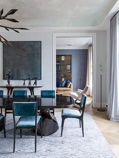 sala de jantar com cadeiras turquesas e tapete com textura