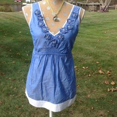 Pretty blue cotton Lilly shirt. Sleeveless blue shirt with flowers. Shirred waist and white band at hem. Neckline is trimmed with blue flowers accented with beads and a pearl center. Lilly Pulitzer Tops Tank Tops
