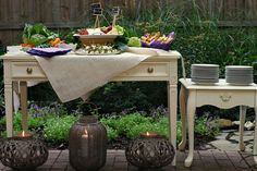 Rustic Garden Party | CatchMyParty.com Suggestion: I would move the candle lanterns away from the front of the table so guests can access the table easier. Since they all hand handles, the large one could go behind the plate table on a Shepherd's hook and the two matching ones could go behind the main food table on pedestals or taller Shepherd's hooks