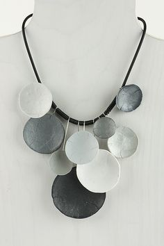 Each concave polymer disc is a different shade of gray. Some has a Mother of pearl sheen. The polymer piece is attached to a stainless steel wire that hangs on a rubber cord with silver clasp. Surprisingly light weight. .