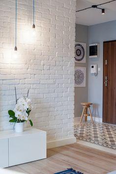 Klimat wnętrza budują m.in. pomalowane na biało ceglane płytki oraz industrialne oświetlenie.