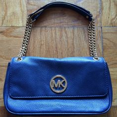 Michael Kors Navy Blue Fulton Shoulder Bag This is a 100% authentic Michael Kors Fulton Shoulder Bag. The outer leather and hardware are in nearly perfect condition. The inner fabric has some spots from wear (please see picture). Overall this bag on the outside looks almost brand new! The straps go on the shoulder and can be let down longer (see picture). MICHAEL Michael Kors Bags Shoulder Bags