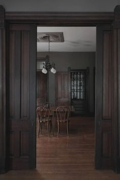 """Says architect and designer Lauren Lochry, """"We restored the woodwork throughout, matching the existing stain. The artistry in the process was matching the historic profiles of the trim in areas that where missing or damaged."""" The interiors are defined by their dark, moody palette. """"Although abstract, we referenced the period of Romanticism in art and painting when selecting the specific paint colors,"""" Lauren says."""