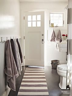 Cozy Country Ranch Home Renovation. Charcoal-gray concrete floors contrast crisply with an otherwise bright white bathroom. The barn-style sconce over the sink is meant for exterior use . Outdoor Pool Bathroom, Pool House Bathroom, Bathroom Doors, Bathroom Ideas, Bathroom Wall, Pool House Decor, Bathroom Towel Hooks, Bathroom Sinks, Downstairs Bathroom
