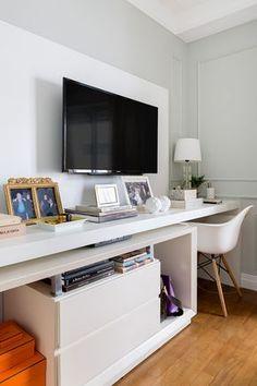 Decoração de apartamento, quarto com parede cinza, aparador branco, TV, porta retrato dourado e adornos.