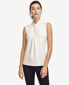 "Twist knot detail puts a modern spin on this wear-now top, rendered in the season's most coveted colors. Twist knot neck. Sleeveless. Back yoke. Hidden back zipper. 25 1/2"" long."