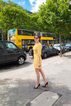 RetroCat wearing a yellow retro dress in the style of the 60s.