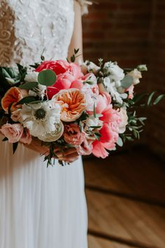 The coral and apricot hues of these peonies paired with white blossoms and eucalyptus branches gives us major vintage wedding vibes. This warm color palette is also perfect for a late summer or early fall wedding! Click for more peony wedding bouquets. // Photo: Grey Lilly Photography