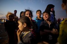 Ahmed, age 5, (right) cries out of fear after crossing into Turkey from Syria with his family Saturday night.  PHOTOGRAPH BY JOHN STANMEYER, NATIONAL GEOGRAPHIC ---------- Photographer Captures Tens of Thousands Fleeing ISIS