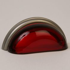 This transparent ruby red glass cabinet/drawer cup pull with traditional design is part of the Glass Bin Pull Series from Lew's Hardware. A hand poured glass bin pull with a brushed nickel finish die cast zinc base. Perfect for use on cabinet doors and drawers capable of accepting a mounted pull, the design transforms the classic all metal fabrication into a unique transitional design with equal use within traditional and modern settings.