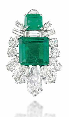 AN ART DECO EMERALD AND DIAMOND BROOCH Of shield design, the square cut-cornered emerald centre weighing approximately 13.37 carats, within an old-cut pear, marquise and cushion shaped diamond border, to a further emerald and baguette-cut diamond surmount, circa 1930.