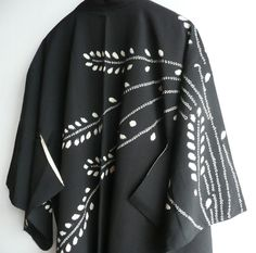 """This is a kimono jacket, """"haori"""". Wheat sheaf pattern is tie dyed. It's wonderfully dynamic and rhythmic design. The black silk fabric has texture of crape. It's crispy and has good body.  There's a pin hole on the back panel of left sleeve, 2"""" (5 cm) from the cuff opening (photo #5 top). The area around the hole is slightly discoloured.  There are a few tiny white stains on the right lapel, about 7"""" (17 cm) above hem (#5 second from top).  There are two brown spots on the tie dyed area…"""