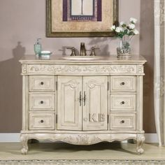 Finding the right cabinet for the right design is key. Elegant and muted, this Empire style vanity adds charm to any bath space. A white oak finish, brass drawer handles, and a Travertine countertop will have your bath be the favorite room of the house!