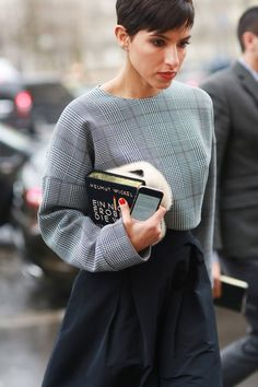 A fun bookish clutch.  #streetstyle at Paris Fashion Week Fall 2014 #PFW