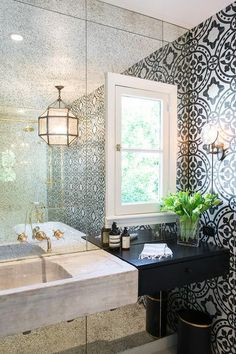 White and black bathroom features an accent wall clad in an antiqued mirror lined with a concrete sink vanity next to black floating vanity drawers. More