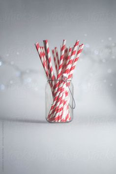 Striped red and white straws in a glass jar with a heart design on the front all on a plain white background with bokeh