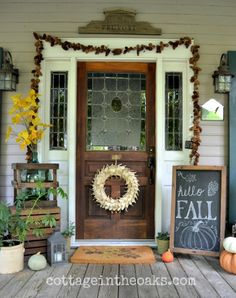 Cottage Front Porch at Cottage in the Oaks: pinecone garland, birch bark wreath, chalkboard, and more! #fall