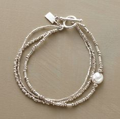 """A luminous freshwater pearl punctuates a rippling rivulet of triple-strand sterling silver beads strung in three different beading arrangements. Made in USA. Exclusive. 7-1/2""""L."""