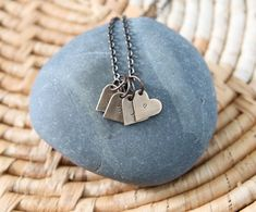 A simple necklace that holds all the hearts you hold in yours. Each heart has a hand stamped initial of a loved one and you can choose how many hearts you need.