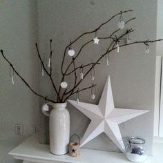 Kerstdecoratie op de schouw. Vaas (VTwonen) met zelfgemaakte hangers van witte klei.