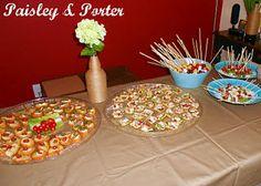 Food table. Left to right, bruschetta, mini steak tacos, Caprese kebabs, fruit salad kebabs