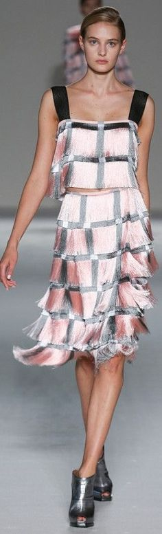 Marco de Vincenzo RTW Spring 2015. A modern influence has a historic style of the 1920's. Evening dresses like this one were short an unfitted with fringe layers all the way down the dress. The dresses came in nearly any and every color. This one is mainly pink, with black incorporations in the straps and bands.
