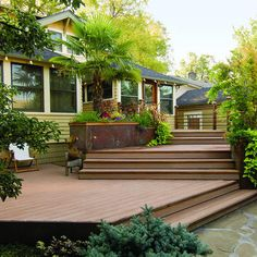 Transitional Deck - Because the house's ground floor sits 3½ feet above ground, the deck needed to provide a gradual descent into the garden. Seven steps connect the deck's three levels to a small ground-level patio with a portable fireplace. There's seating on the top and bottom levels, and storage beneath the deck for the couple's canoes.
