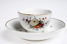 Kopp med fat 1776-90. Koppen slät, uppåt vidgande. Polykrom blomsterdekor. Mynningsrand i guld på kopp och fat.