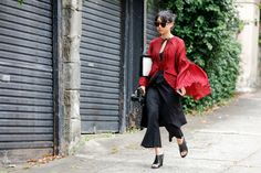 Margaret Zhang wears red pleated flare sleeve blouse with black flare pants and black mules
