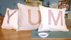 Turn over old throw pillow and use the back for your new surface.    Use safety pins of bright colors and create a letter, or design, on the pillow.