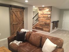 Barn doors and pallet wall in the basement. Walls are Agreeable Gray by Sherwin Williams.