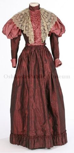 1890s dress made with two different cranberry-colored silk fabrics. The skirt, bodice arms, stand-up collar, and body as well as part of braid-like fabric twist at waist are in a dark red cranberry-color iridescent (shot) fabric with a tiny white and gray grid pattern print. The bodice front, top puff of leg-of-mutton-style sleeves, sleeve cuffs, and part of braid-like fabric twist at waist are a pattern of tiny teardrops and polka dots in a pinkish cranberry and pink.