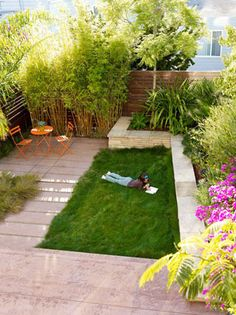 Grassy nook, outdoor living and garden around this small urban pretty backyard landscape