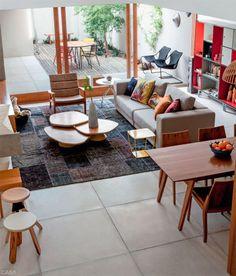 A mesa de centro é uma composição dos modelos Folha e Trevo. Poltrona Theo (peças de Fernando Jaeger). No trecho externo, junto ao muro, cadeiras Paulistano, de Paulo Mendes da Rocha (Futon Company).