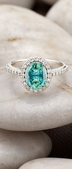 An intricate halo of pavé-set diamonds embraces and accentuates the vibrant gemstone of this brilliant engagement ring. ==