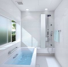 With an elongated tub working alongside a shower corner that includes a spa-quality spout and narrow full-length mirror, this bathroom packs a lot of punch for its small square footage. A window even lets in fresh air, barred with bushes for privacy. Note the simplicity of the detailing, including the lighting above.